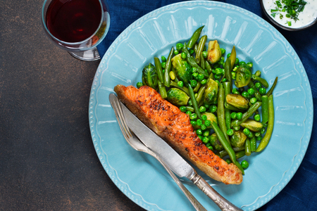 Baked salmon steak with asparagus, Brussels sprouts and green peas on a concrete background with a glass of wine.