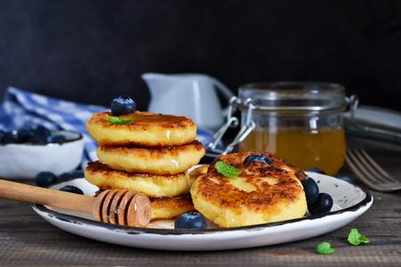 Classic Russian breakfast - cheesecake with honey and berries. Stock Photo