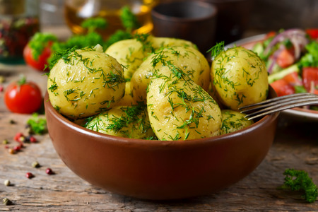 Young, boiled potatoes with butter and dill on a wooden background.