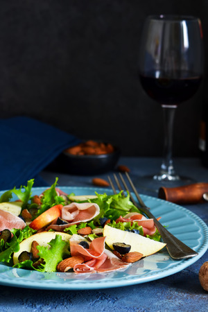 Salad with jamon, pears, blueberries and almonds. A glass of cold, red wine. Delicacy.