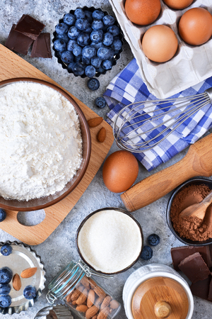 Food background. Ingredients for baking: flour, eggs, berries, chocolate on a concrete background. Foto de archivo - 105307038