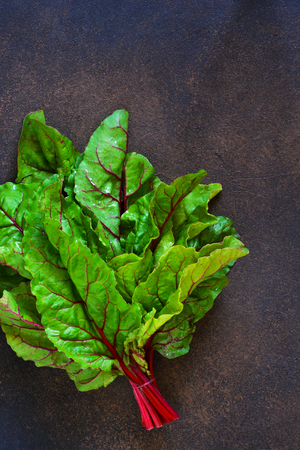 Fresh, raw leaves of the beetroot on a concrete background. Food background. Stock Photo