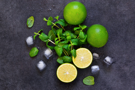 Fresh mint, lime and ice on a black background. Ingredient for mojito. Top view