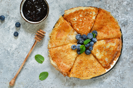 Thin pancakes with blueberry jam on a concrete background with poxt space.