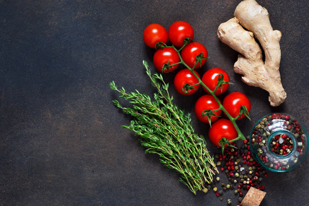 Tomato, ginger and a variety of spices on a dark background.