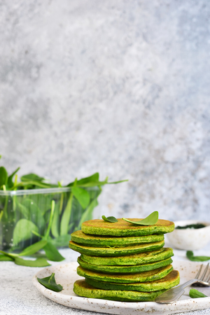 Green pancakes with spinach on a light concrete background. Classic breakfast.