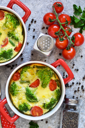 Casserole with broccoli and tomatoes on a concrete background. View from above.