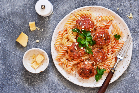Italian pasta with meat balls, tomato sauce and parmesan on a concrete background.