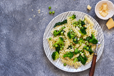 Italian pasta with spinach, broccoli and green peas on a concrete background. Dinner time. Top view. Stock fotó