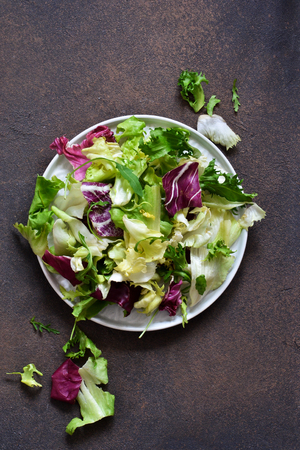 Fresh mix of salads: lettuce, arugula, spinach, mesclun, mache on a dark background. Top view. Banco de Imagens