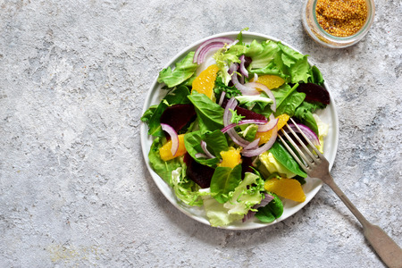 Mixed salad with orange, beetroot and sauce on the kitchen table. Organic Food. Vegan.
