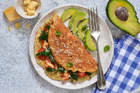 Omelet with tomatoes, cheese and basil in a plate on the kitchen table. View from above.