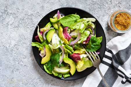 Fresh mix salad with avocado and sauce on a concrete background. View from above.