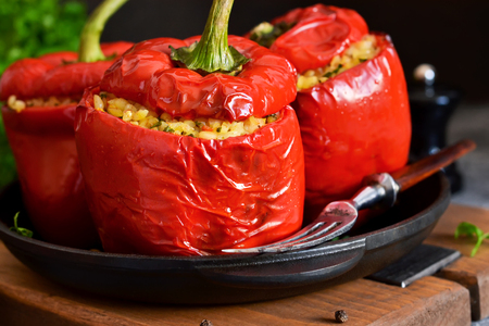 Red pepper stuffed with meat, bulgur and vegetables in a cast-iron pan. Baked stuffed peppers.