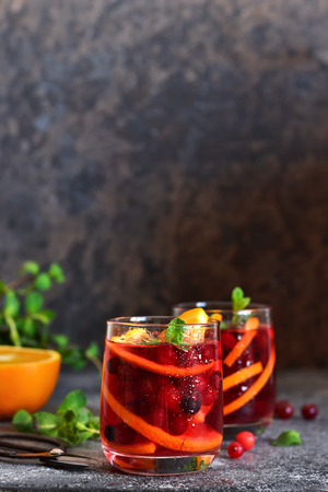 Cold cranberry juice with orange and mint. Summer drink.