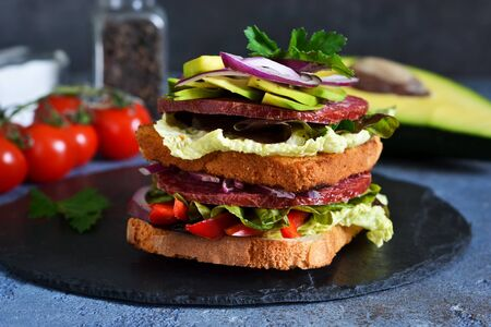Crispy sandwich with salami, salad and vegetables on the kitchen table. View from above.