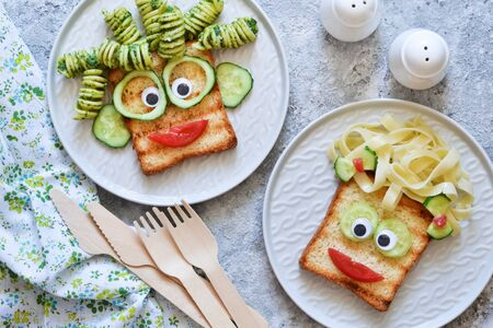 Funny faces - lunch for the child. Sandwich with vegetables. View from above. Фото со стока