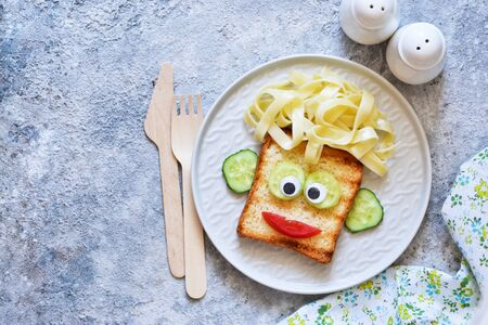 Lunch for children. Pasta with sandwiches and vegetables. Cheerful face. Фото со стока