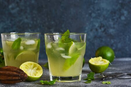 Summer cold drink - majito with lime and mint on a concrete dark background.
