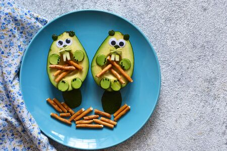 Lunch for the child. Funny beavers from avocado in a plate on a concrete background.