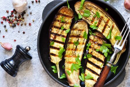 Spicy eggplant grilled in a cast-iron frying pan on a concrete background.