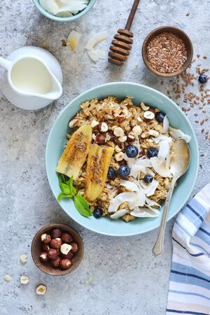 Oatmeal with caramel, banana, blueberries and coconut chips on a concrete background.
