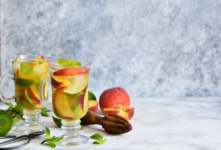 Cold summer drink with peach, lime and mint on a concrete background.