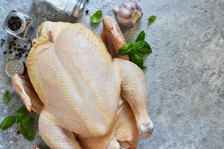 Fresh, raw chicken with spices and basil on the kitchen table. View from above. Stockfoto