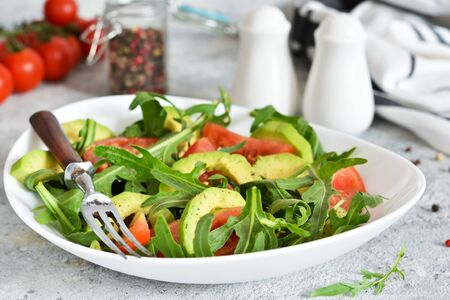 Salad with rucolla, tomatoes, avocado and sauce on the kitchen table. The view is close.