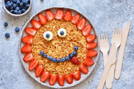Food for children. Funny sun with a smile - pancakes with berries.