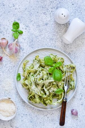 Tagliatelle with pesto on the kitchen table. View from above. Reklamní fotografie