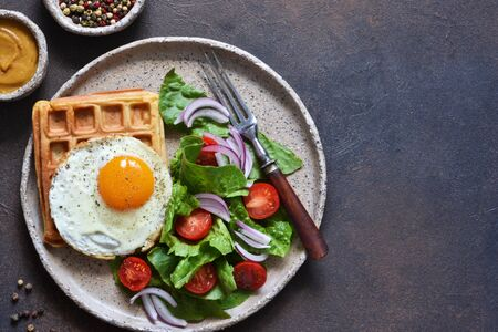 Belgian waffles with egg and salad for breakfast in a plate on the kitchen table. View from above. Imagens