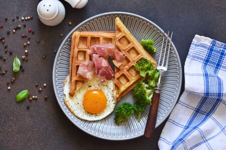 Belgian waffles for breakfast with egg, prosciutto and broccoli on a dark background.