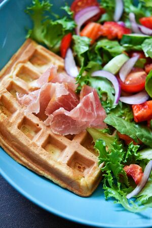 Belgian waffles with prosciutto and vegetable salad on the kitchen table.