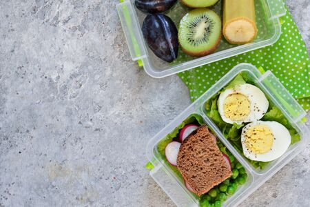 Two lunch boxes with sandwich and egg. Dsert-fruit. Top view. Stockfoto