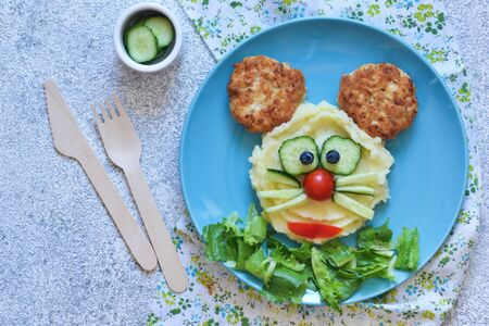 Funny little mouse for kids lunch. Food for children: mashed potatoes, burger, salad.