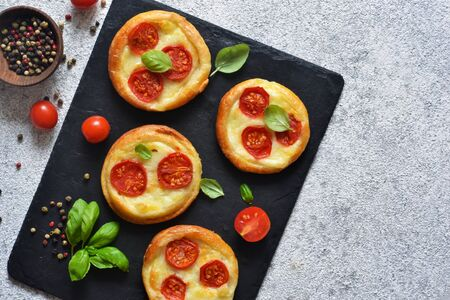 Mini pie with tomatoes and cheese. Quiche with vegetables and sauce top view. Imagens
