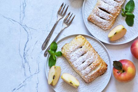 Puffs with apples and cinnamon in a plate on the kitchen table. View from above! Stock Photo
