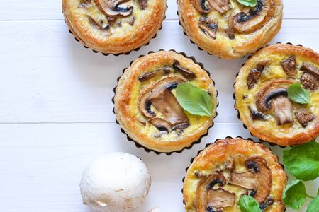Tartlets with mushrooms and chicken on a wooden background. View from above.
