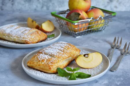 Blätterteig mit Äpfeln und Zimt in einem Teller auf dem Küchentisch. Standard-Bild