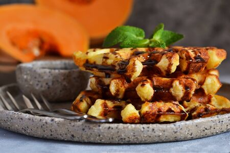 Belgian waffles with pumpkin and chocolate sauce on a concrete background with place for text.
