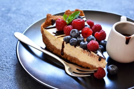 Gâteau au fromage à la vanille fait maison avec sauce au chocolat et baies sur fond de béton. Banque d'images