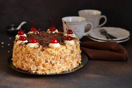Chocolate cake with vanilla cream, cherry and almonds on a dark background.