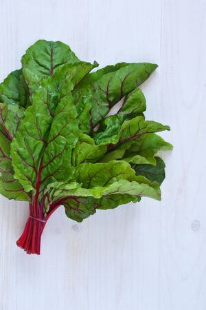 Fresh, raw leaves of the beetroot on a concrete background. Food background. Imagens