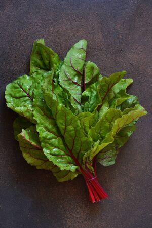 Frische, rohe Blätter der Rote Beete auf einem konkreten Hintergrund. Lebensmittelhintergrund.