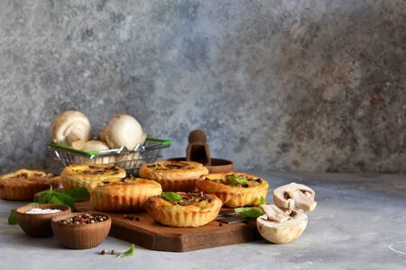 Puff pastry cake with mushrooms on a concrete background.