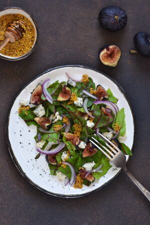 Vitamin salad with figs and blue cheese on a warm background.