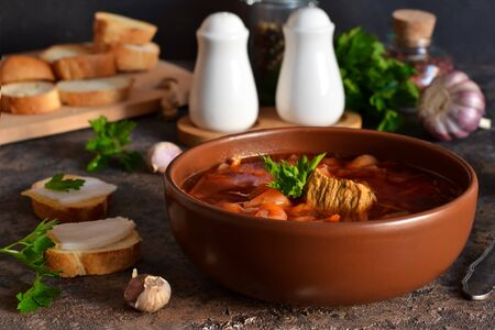 Borsch - a national dish of Russian cuisine with lard on the kitchen table. Vegetable soup with beets and meat. Zdjęcie Seryjne