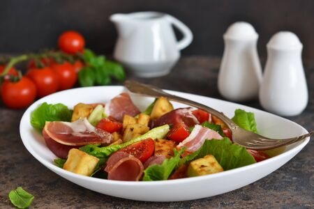 Salad with tomatoes, prosciutto and grilled cheese on a stone background.