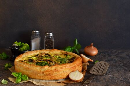 Quiche with mushrooms, onions and broccoli on a concrete background. Pie with mushrooms.